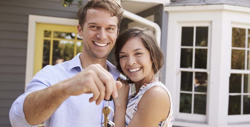 happy couple holding the keys to their new home