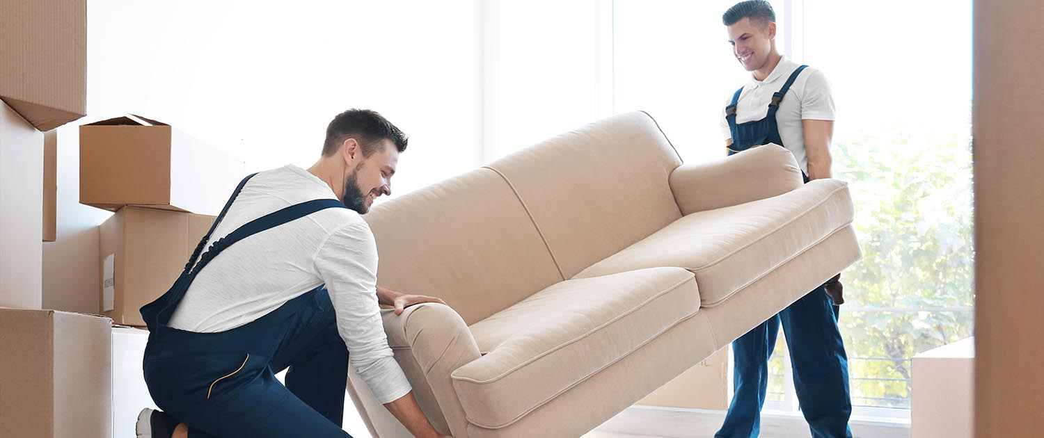 two men working for a moving company carrying a couch indoors