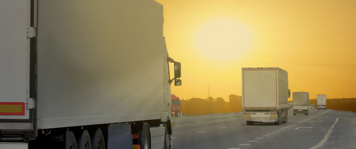 rear view of four moving trucks on the interstate at dusk