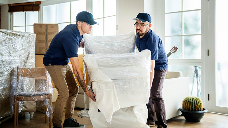 moving companies iowa two men moving a padded and shrink wrapped chair