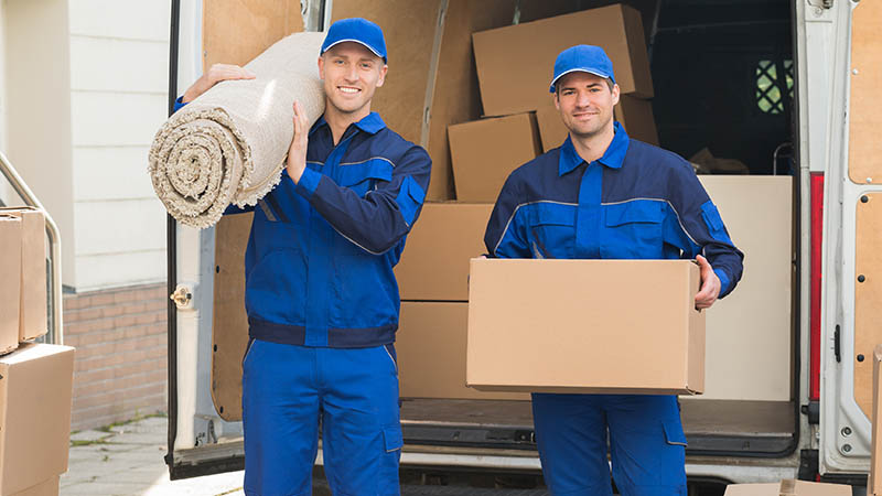 two cross country movers in iowa standing in front of moving van holding a roll of carpet and a box smiling