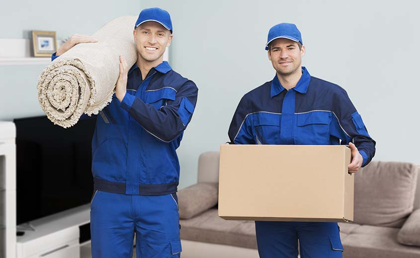 two movers in the living room holding a rug and a box